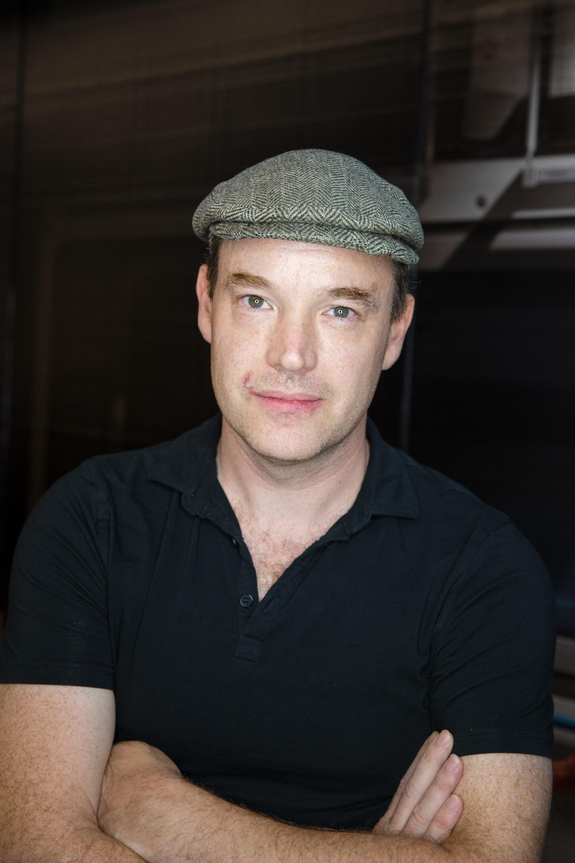 An upper-body shot of Owen. He has dark hair and blue eyes and is wearing a grey beret and a dark polo shirt. His arms are crossed.