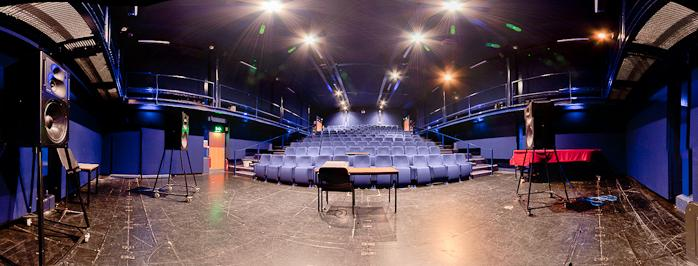 A panoramic view of the Rymer auditorium from the stage. The walls are blue, the floor is dark brown. There are 3 large loudspeakers visible with a table in the centre of the stage. Lines of blue fold-down chairs can be seen in tiers going towards the back of the room with steps up each side.
